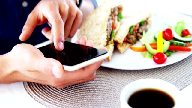 Man-in-lunch-bar-with-smartphone-and-coffee