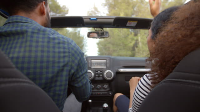 Couple-Driving-Open-Top-Car-On-Country-Road