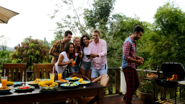Young-People-Talking-Using-Cell-Smart-Phones-While-Latin-Man-Cooking-Barbecue-Friends-Group-Cheerful-Dancing-Gathering-On-Summer-Terrace