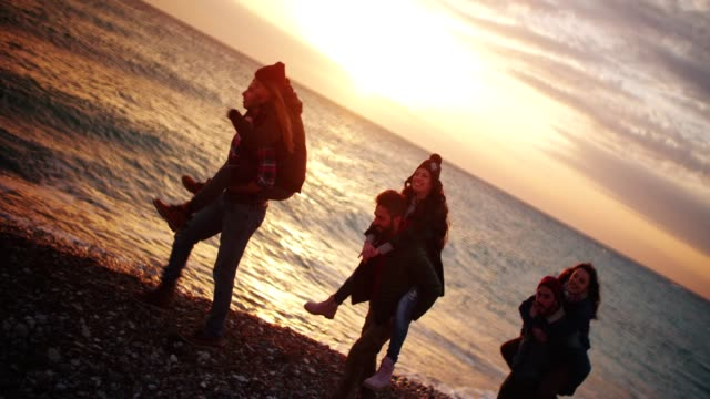 Friends-giving-piggy-back-rides-on-a-beach-at-sunset
