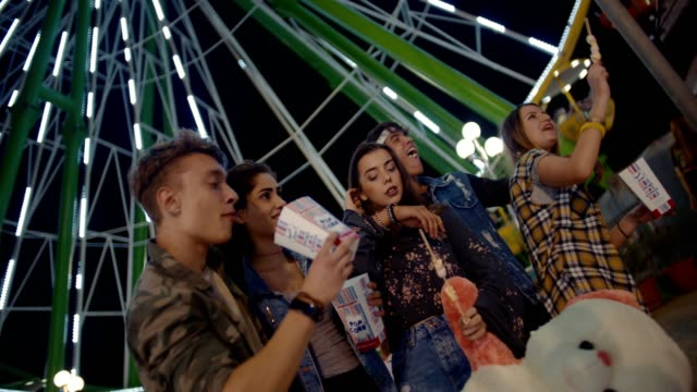 Teenage-friends-having-fun-on-night-out-at-amusement-park