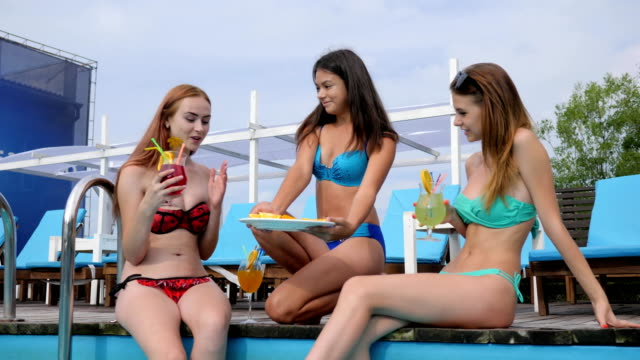 Summer-vacation-of-Young-friends-at-resort-in-Swimming-pool-Beautiful-girlfriends-in-swimsuits-Drink-beverage