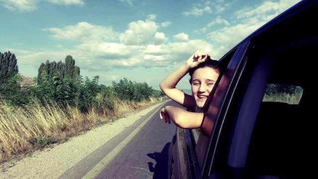 Chica-coche-en-carretera-viaje-saludando-bailando-cantando-sonriendo-feliz-por-la-ventana