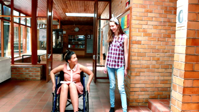 School-girl-interacting-with-her-disabled-friend-in-corridor