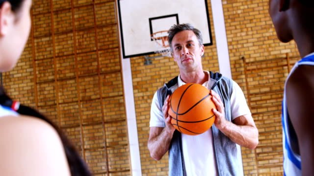 Coach-assisting-schoolkids-in-basketball-4k