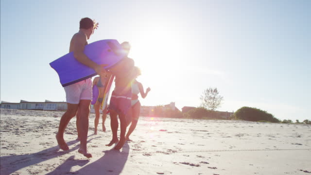 Multi-ethnic-males-and-females-jogging-with-bodyboards