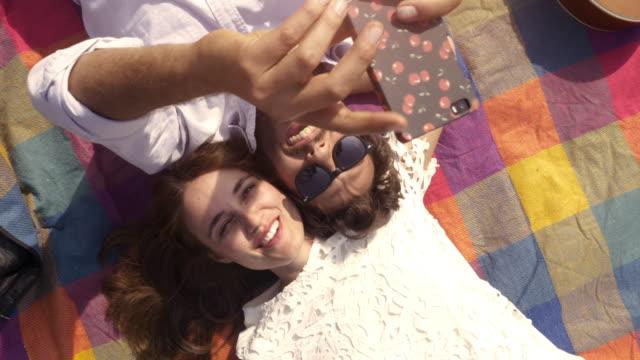 Schöne-junge-Brautpaar-auf-bunte-Decke-im-Park-unter-Selfies-Smartphone-romantisch-mit-Gitarre-Sonnenbrillen-liegen-schöne-attraktive-Mädchen-Draufsicht-rotierende-Kamera-Slow-Motion