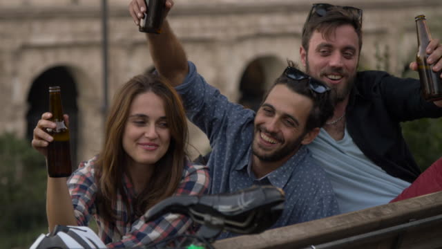 Tres-turistas-jóvenes-amigos-con-bicicletas-sentado-sobre-un-banco-frente-a-Coliseo-bajo-el-árbol-en-la-puesta-de-sol-beber-cervezas-diversión-hablando-riendo-a-refrigeración-en-cámara-lenta-de-Roma