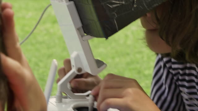 Young-little-girl-flying-a-drone-playing-outdoor-on-summer-in-green-grass-field-remote-pilot-slow-motion
