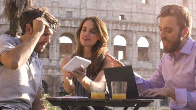 Three-young-people-working-together-on-a-project-with-laptop-and-tablet-brainstorming-writing-talking-and-researching-new-ideas-sitting-at-bar-restaurant-table-in-front-of-colosseum-in-rome-at-sunset