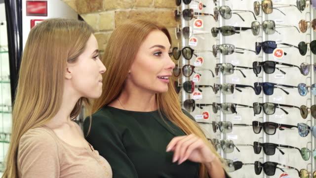 Dos-hermosas-mujeres-jóvenes-elegir-gafas-en-la-tienda-de-óptica
