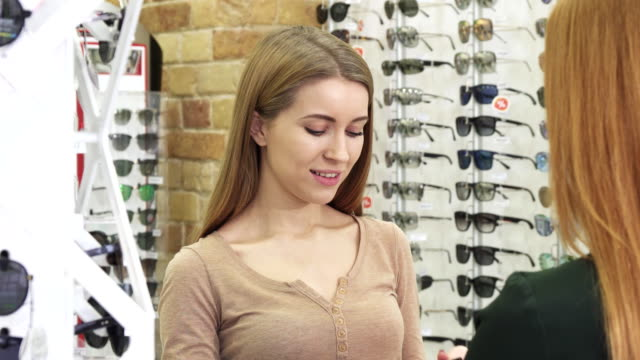 Happy-young-beautiful-woman-trying-on-sunglasses-at-the-optics-store
