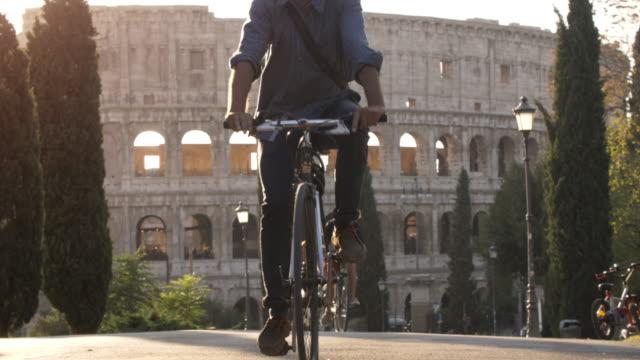 Drei-junge-Freunde-Touristen-Reiten-Fahrräder-in-Colle-Oppio-Park-vor-Kolosseum-auf-Straße-mit-Bäumen-bei-Sonnenuntergang-in-Rom-Slow-motion