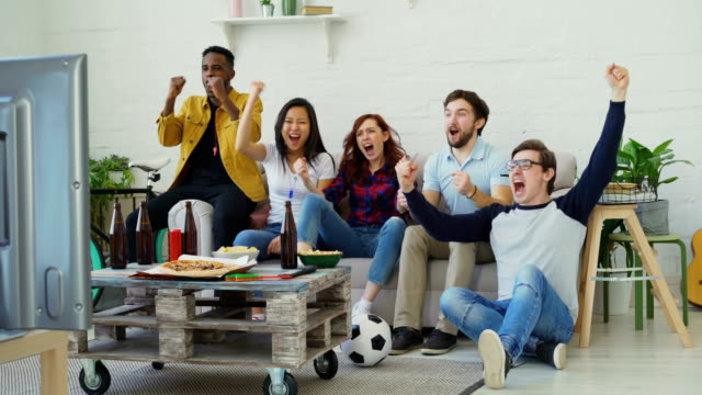 Gruppe-der-happy-Friends-Sportspiel-im-Fernsehen-zu-Hause-beobachten-Sie-freuen-sich-über-ihre-Lieblings-Team-gewinnen-Wettbewerb