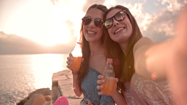 Adolescentes-hipster-tomar-autorretratos-y-bebiendo-refrescos-en-la-playa