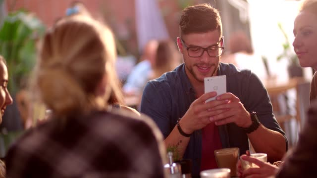 Happy-hipster-man-texting-on-smartphone-while-in-a-cafe