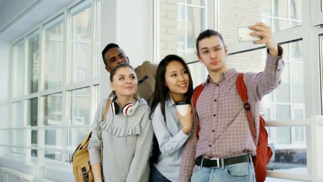 Grupo-de-estudiantes-multiétnicos-selfie-en-smartphone-cámara-mientras-está-parado-en-el-pasillo-de-la-Universidad-Chico-hipster-con-teléfono-y-amigos-plantean-positivamente