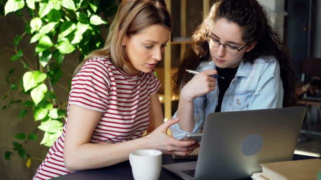 Primer-plano-de-dos-alumnas-con-teléfono-inteligente-Chica-rubia-atractiva-pantalla-táctil-y-charlando-con-su-amigo-Tecnología-moderna-para-el-concepto-de-gente-joven-