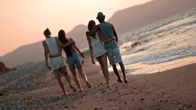 Romantische-multiethnischen-Hipster-Paare-zu-Fuß-am-Strand-bei-Sonnenuntergang