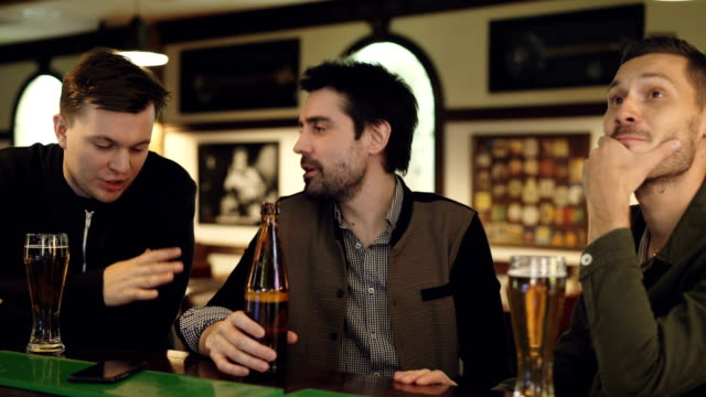 Cheerful-handsome-guys-are-having-conversation-in-bar-over-beer-Young-men-are-holding-bottles-and-glasses-chatting-and-gesturing-emotionally-