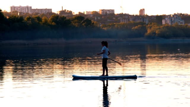 Long-Shot-Beautiful-Girl-with-Oars-Sails-on-the-River-Standing-on-Sup