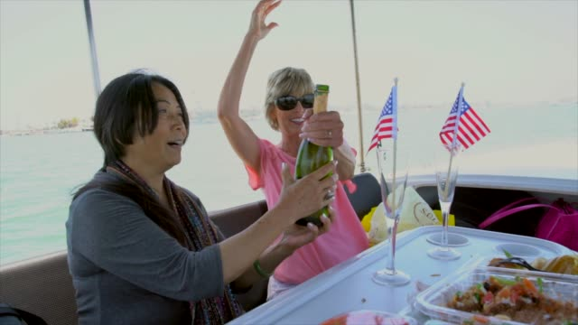 multiracial-older-women-opening-champagne-and-celebrating-on-a-boat