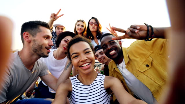 Point-of-view-shot-of-African-American-girl-holding-camera-and-taking-selfie-with-happy-friends-at-party-on-roof-Men-and-women-are-looking-at-camera-posing-and-laughing-