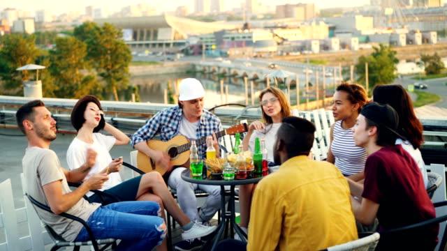 Los-jóvenes-divierten-en-tejado-tocando-la-guitarra-cantando-charlando-y-riendo-sentado-en-mesa-al-aire-libre-Concepto-de-alegría-música-juventud-y-amistad-