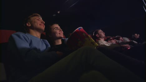 Love-couple-kissing-in-cinema-Romantic-couple-embracing-in-movie-theatre