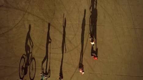 Teenagers-riding-one-by-one-on-wheeled-vehicles-Top-view-children-cast-long-shadows