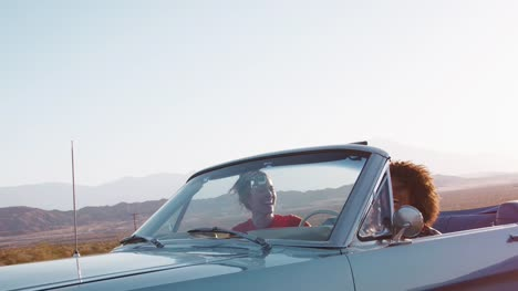 Laughing-female-friends-driving-in-convertible-on-a-highway