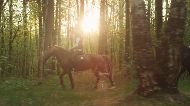 Two-Young-Girls-Riding-Horses-in-Forest