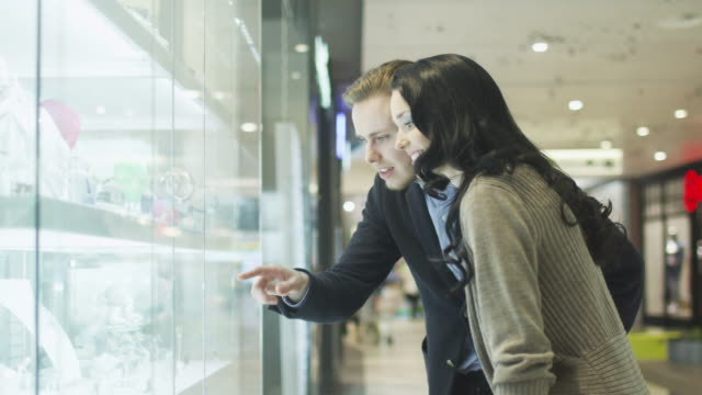 Young-Couple-is-Looking-at-Display-Window-of-Jewellery-Store-in-Shopping-Mall-