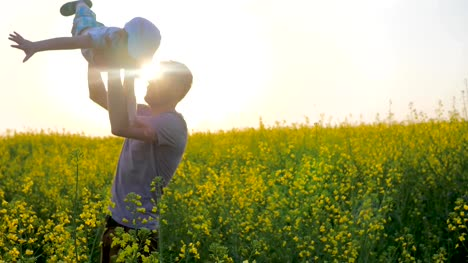 Joyful-boy-at-hands-parent-in-form-of-airplane-at-field-daddy-with-son-at-arms-played-into-meadow-flowers