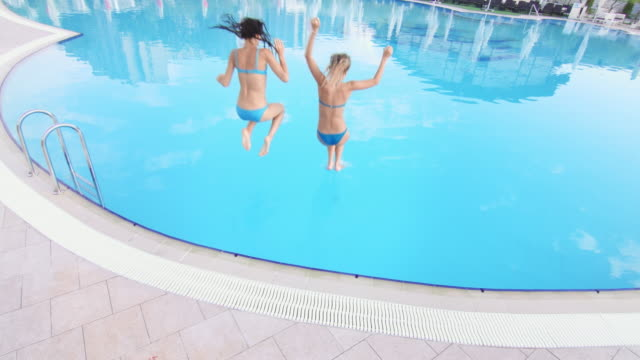 Two-girls-jump-in-swimming-pool-wide-shot