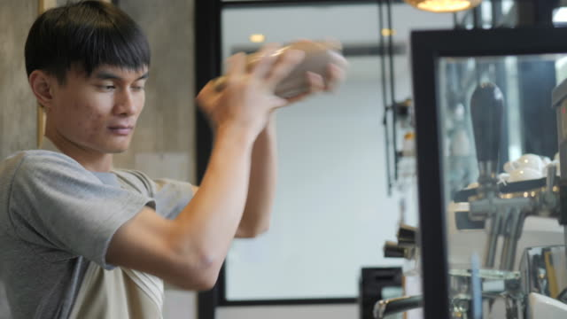 Young-asian-barista-shakes-a-shaker-in-cafe-in-slow-motion