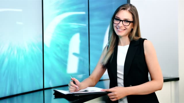 European-female-stylish-news-presenter-in-broadcasting-studio-medium-shot