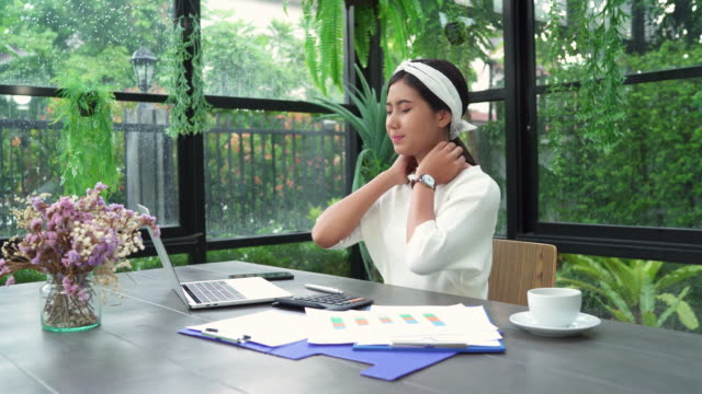 Beautiful-young-smiling-asian-woman-working-on-laptop-while-sitting-in-living-room-at-home-Asian-business-woman-working-document-finance-and-calculator-in-her-home-office-Enjoying-time-at-home-