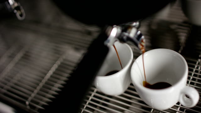 Super-slow-motion-of-hot-espresso-coffee-pouring-into-a-two-white-porcelain-cups-from-coffee-machine-in-4k-(-top-view-close-up)