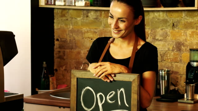A-coffee-shop-worker-holds-a-Open-sign-