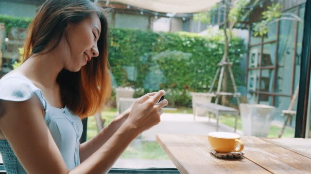 Female-blogger-photographing-coffee-cup-in-cafe-with-her-phone-A-young-woman-taking-photo-of-coffee-tea-on-smartphone-photographing-meal-with-mobile-camera-
