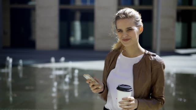 Beautiful-blonde-woman-with-disposable-coffee-cup-and-cell-phone-in-her-hands-posing-near-fountain-in-street-and-smiling-happily-at-camera-medium-shot