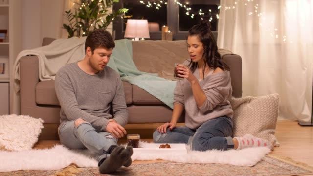 pareja-feliz-bebiendo-café-y-comiendo-en-casa