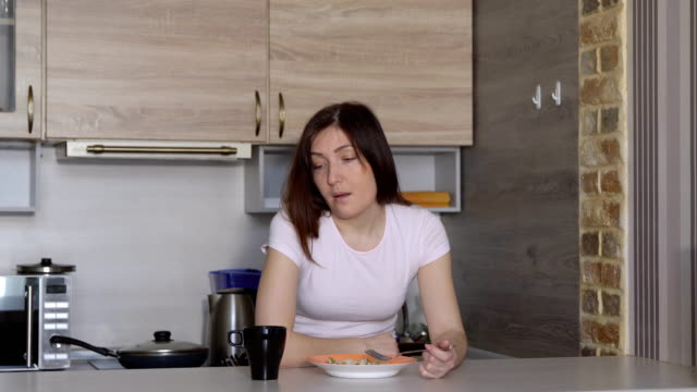 Young-woman-falling-asleep-eating-at-the-table-in-the-kitchen
