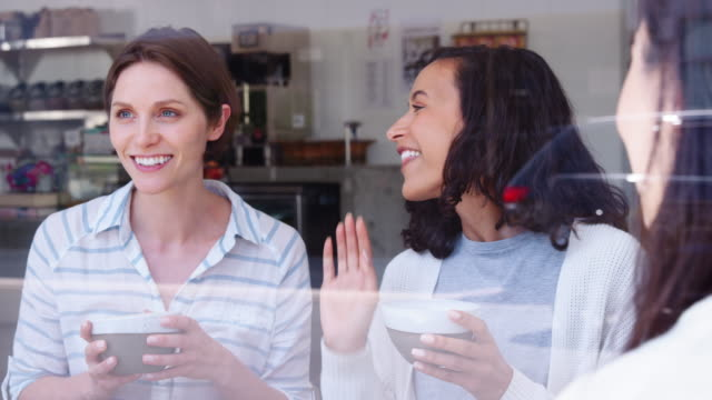 Female-friends-laughing-at-coffee-shop-seen-through-window