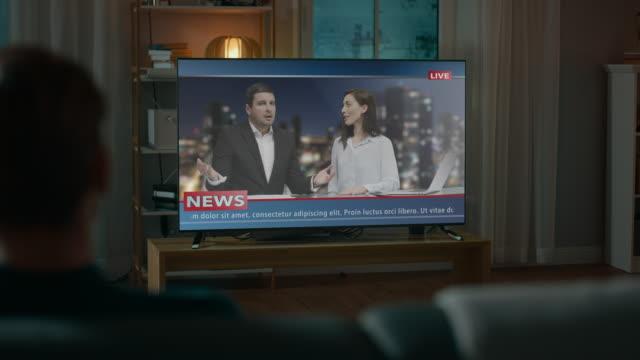Hombre-relojes-Late-Night-noticias-Show-en-la-televisión-sentado-en-un-sofá-en-la-casa-por-la-noche-Dos-presentadores-hablaran-y-bromear-en-la-TV-Acogedor-living-con-luces-cálidas-Sobre-el-tiro-de-hombro-