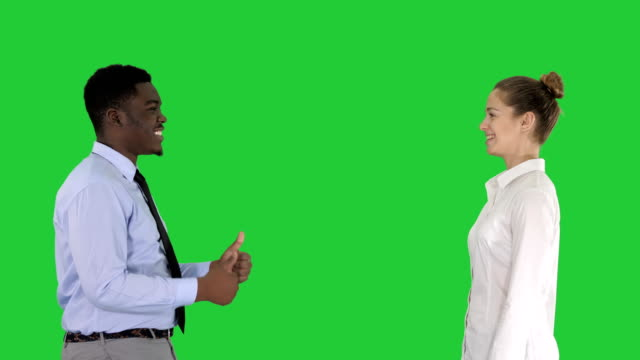 Young-woman-and-young-man-in-formal-clothes-give-high-five-on-a-Green-Screen-Chroma-Key
