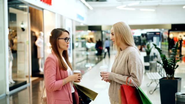 Happy-female-students-are-chatting-and-laughing-standing-together-in-shopping-mall-with-bags-and-takeaway-drinks-Fashionable-clothing-on-mannequins-is-visible-