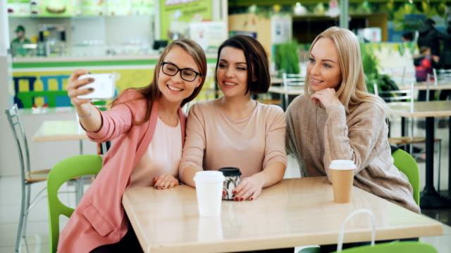 Hermosas-señoritas-toman-selfie-con-smartphone-sentado-en-la-mesa-de-café-y-posando-con-bebidas-Amistad-ocio-y-concepto-de-la-tecnología-moderna-