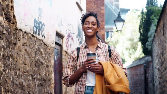 Young-black-woman-wearing-a-plaid-shirt-standing-in-an-alleyway-holding-her-coat-and-a-takeaway-coffee-smiling-to-camera-close-up